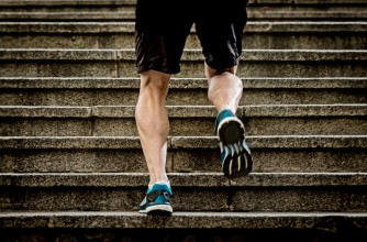 legs of young sport man with sharp scarf muscles running on staircase steps jogging in urban training